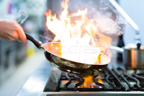 Chef in restaurant kitchen at stove with pan Stock photo © Kzenon