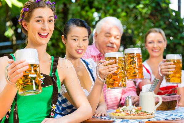 In Beer garden - friends drinking beer in bavaria Stock photo © Kzenon