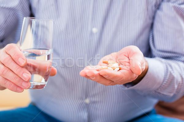 Senior taking overdoses pills at home Stock photo © Kzenon