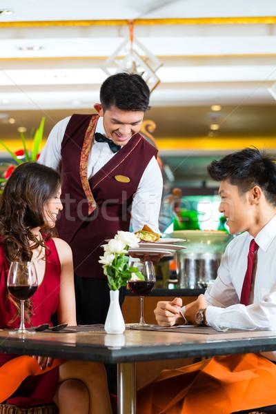 Stock photo: Chinese waiter serving dinner in elegant restaurant or Hotel