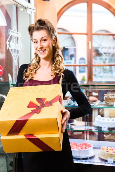 Nő bemutat dobozok cukrászda torta sütemények Stock fotó © Kzenon