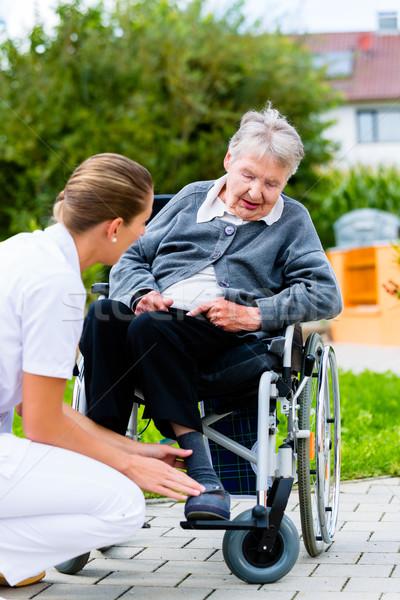 Foto stock: Enfermeira · empurrando · senior · mulher · cadeira · de · rodas · andar