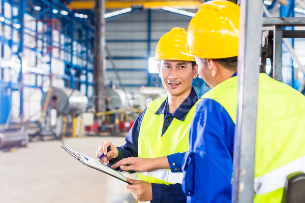 Worker and forklift driver in industrial factory Stock photo © Kzenon