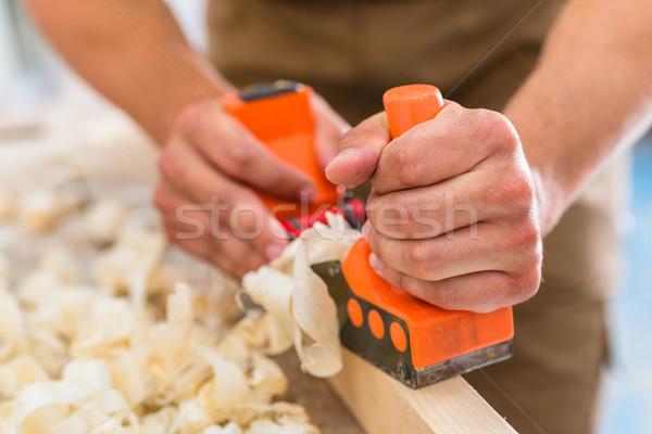 Carpenter with wood planer working on piece Stock photo © Kzenon