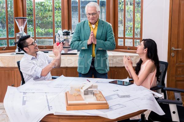 Successful senior architect congratulated by his colleagues Stock photo © Kzenon