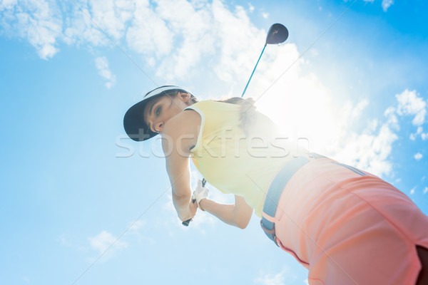 Female professional player holding up the iron club while playing golf Stock photo © Kzenon
