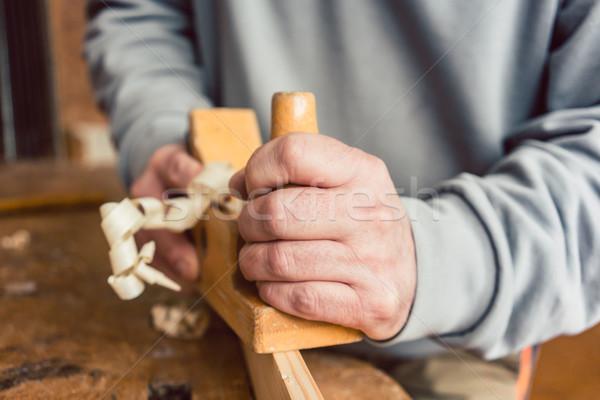 Hand of a senior carpenter with wood planer Stock photo © Kzenon