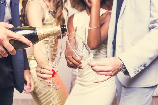 Man pouring sparkling wine into glass of his celebrating friends Stock photo © Kzenon