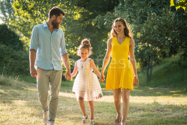 Caring parents holding hands of daughter while walking together  Stock photo © Kzenon