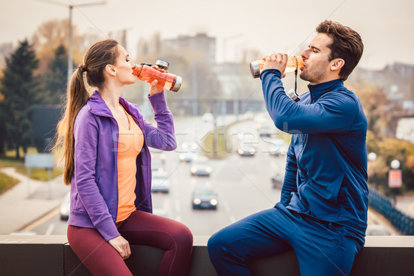 Woman and man drinking water in break from fitness training Stock photo © Kzenon