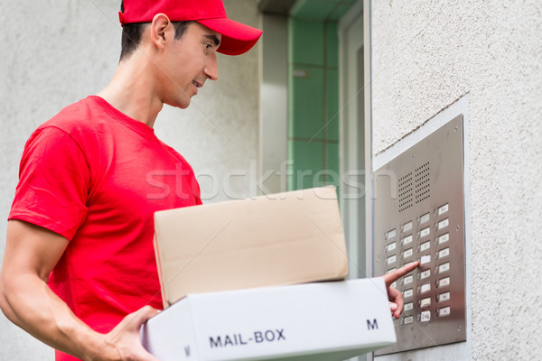 Delivery man carrying mail packages using the intercom Stock photo © Kzenon