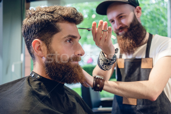 Dedicated hairstylist using scissors and comb Stock photo © Kzenon