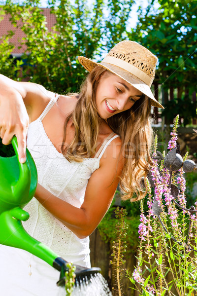 Woman gardener watering flowers in garden Stock photo © Kzenon