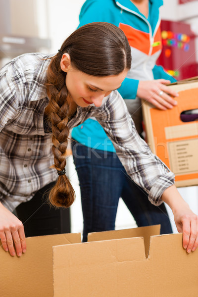Two women with moving box in her house Stock photo © Kzenon