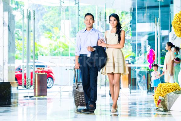 Asian couple arriving in hotel lobby Stock photo © Kzenon