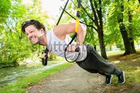 Homem cidade parque suspensão treinador esportes Foto stock © Kzenon