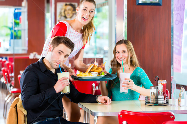Stock photo: People in American diner or restaurant eating fast food