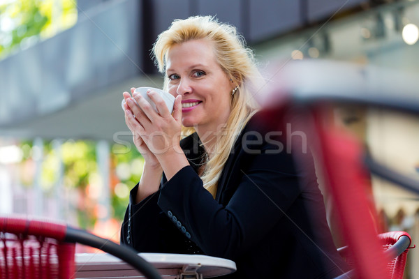 Woman drinking coffee outside in city cafe Stock photo © Kzenon