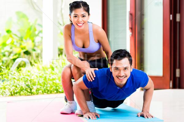 Asian woman helping man with push-up Stock photo © Kzenon