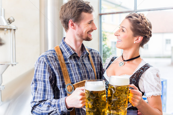 Brewer and woman toasting in beer brewery Stock photo © Kzenon