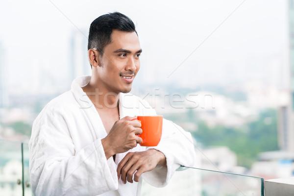 ázsiai férfi reggel elöl városkép iszik Stock fotó © Kzenon