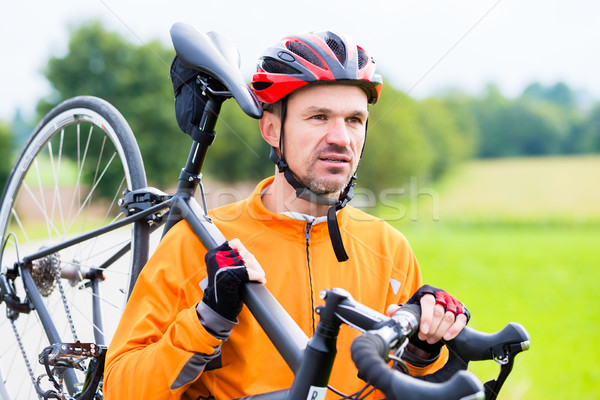 Cyclist carrying his bike over shoulder Stock photo © Kzenon