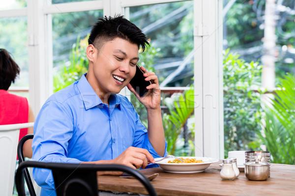 Young Asian man chatting on his mobile Stock photo © Kzenon