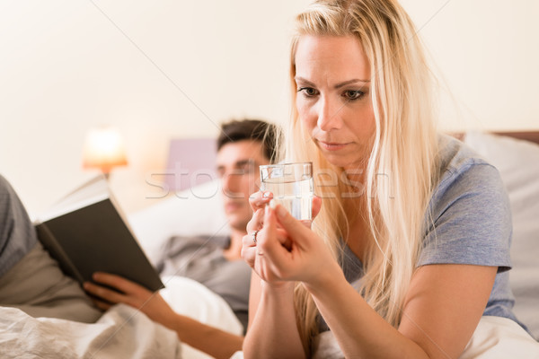 Worried woman taking a pill before sleep at night  Stock photo © Kzenon