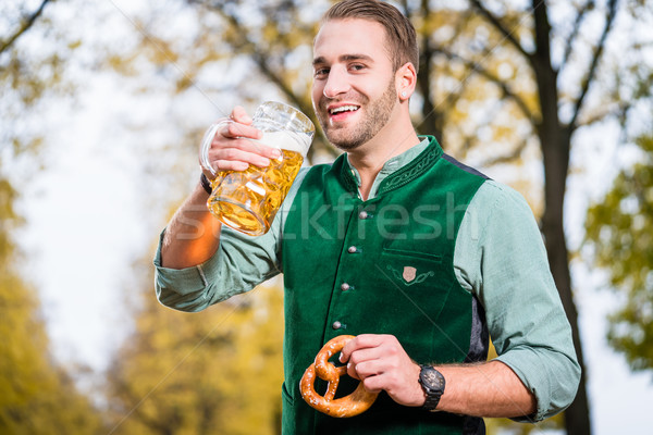 Man in traditional bavarian Tracht drinking beer out of huge mug Stock photo © Kzenon