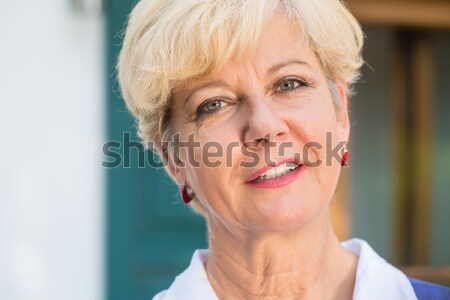Close-up portrait of an elegant senior woman looking at camera w Stock photo © Kzenon