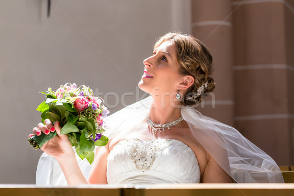 Bride at wedding in church with flower bouquet Stock photo © Kzenon