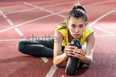woman athlete stretching on racing track before running Stock photo © Kzenon