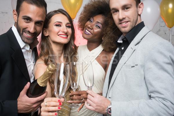 Férfi új év születésnapi buli nyitás üveg pezsgő Stock fotó © Kzenon