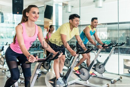 Fit women burning calories during indoor cycling class in a mode Stock photo © Kzenon