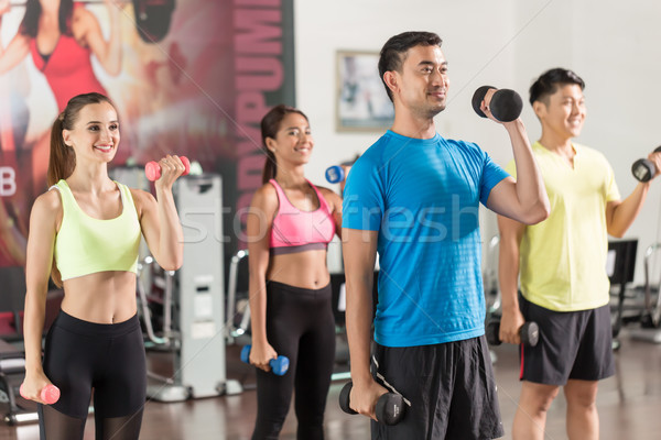 Fit handsome man smiling while exercising bicep curls Stock photo © Kzenon