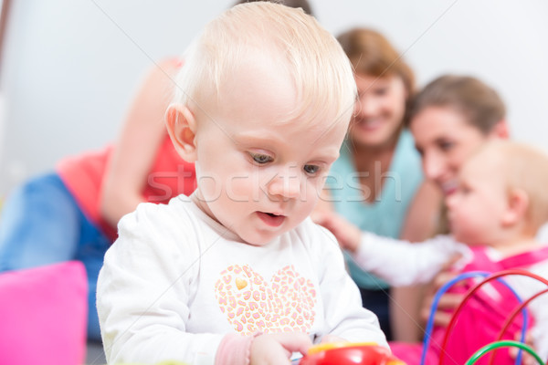 Portrait of a cute blond baby girl playing with colorful toys Stock photo © Kzenon