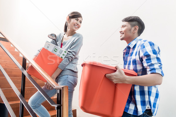 Young indonesian couple in stairway carrying removal crate Stock photo © Kzenon