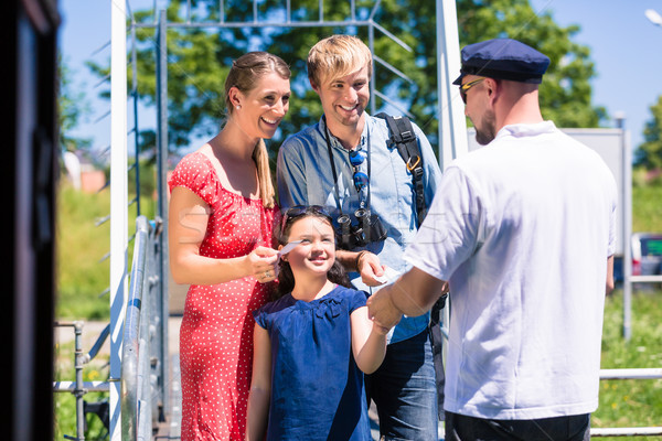 Family buying tickets for river cruise from boatman Stock photo © Kzenon