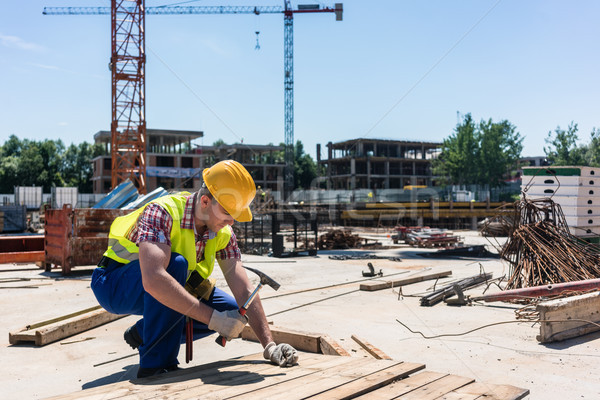 Side view of a young worker hammering a nail into wood during work Stock photo © Kzenon