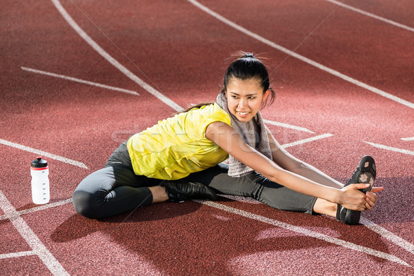 Woman sprinter doing warm up exercise before sprint Stock photo © Kzenon