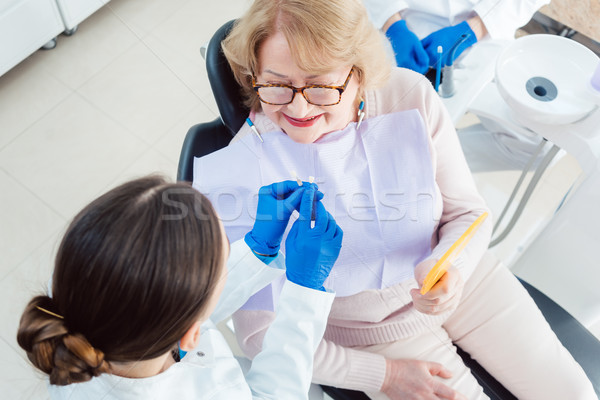 Dentist explain dental bleaching to patient  Stock photo © Kzenon