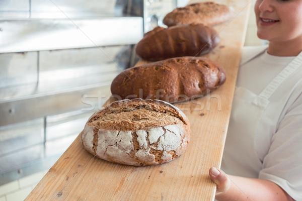 Fresh bread on a board in bakehouse of bakery Stock photo © Kzenon