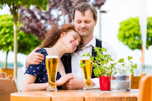 Couple in love cuddling in beer garden Stock photo © Kzenon