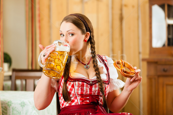 Young woman in traditional Bavarian Tracht in restaurant or pub Stock photo © Kzenon