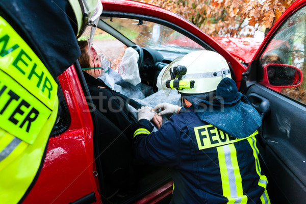 Accident - Fire brigade rescues Victim of a car crash Stock photo © Kzenon