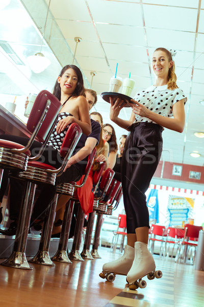 People in American diner or restaurant with waitress Stock photo © Kzenon