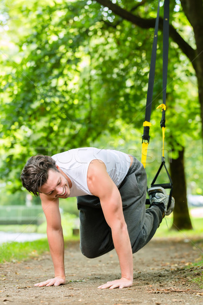 Hombre ciudad parque suspensión entrenador deporte Foto stock © Kzenon