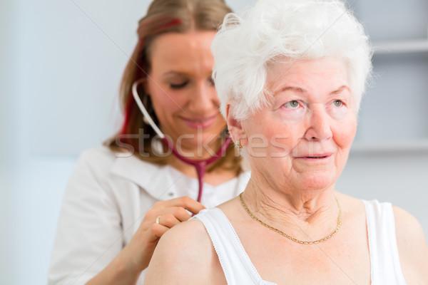 Doctor auscultating senior patient in practice Stock photo © Kzenon