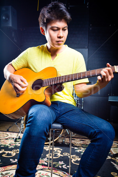 Asian guitarist playing music in recording studio  Stock photo © Kzenon