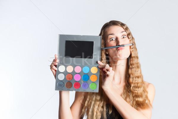 Woman put make-up on having fun Stock photo © Kzenon